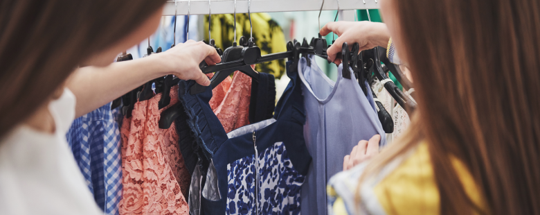 Two women look through a store clothing rail during a retail market research shopper insights research project