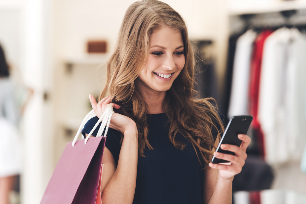 Woman shopping in a clothes store and submitting shopper insights via her phone as part of retail market research