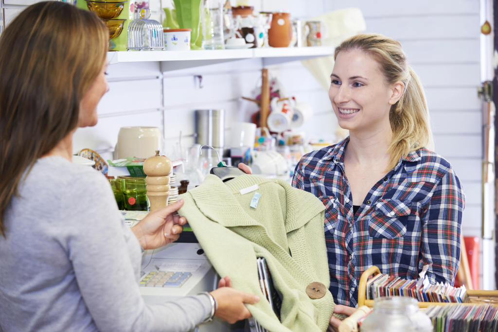 A customer buying clothing in a charity shop take part in charity market research projects near you
