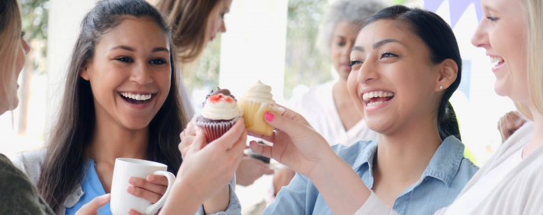 Friends toasting cupcakes at a charity event take part in charity market research projects near you