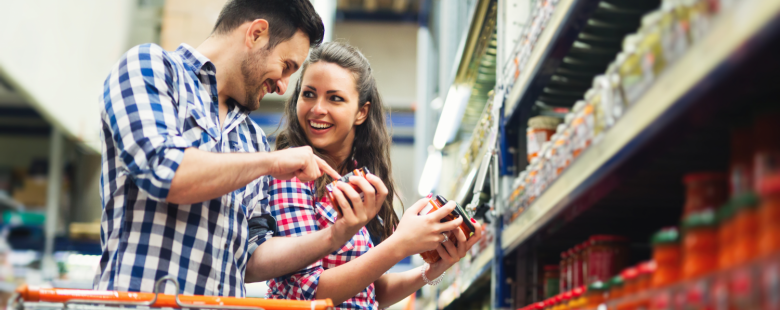 Couple using trolley shopping in store for food and ingridients as part of consumer and shopper insights research